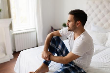 Droevige mensenzitting op bed die over problemen denken