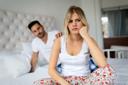 Young unhappy couple in bed having problems and crisis