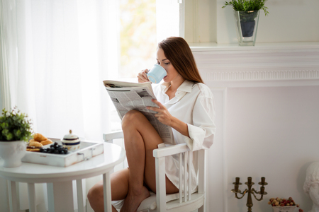 집에서 잡지를 읽는 평화로운 젊은 여성