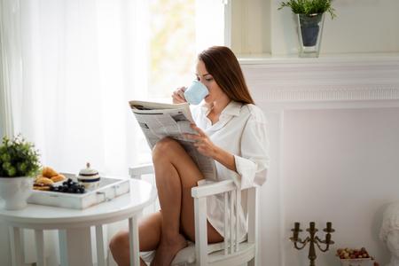 koncentrovaný: Pokojně mladá žena čte časopis doma