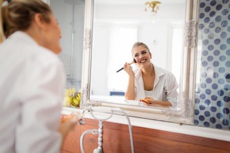 Beautiful girl in bathroom applying makeup Stock Photo