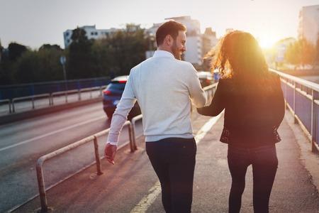 手をつないで歩いて幸せな若いカップル
