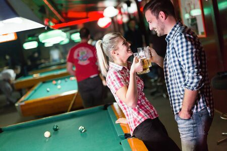 billiard: Happy couple drinking beer and playing snooker