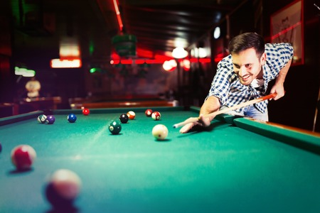 Hansome man playing pool in bar alone Stock Photo