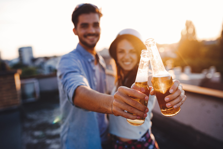 Young happy couple toasting with beer outdoors Stock Photo