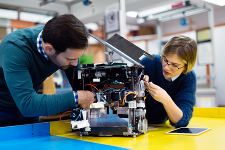 Young students of robotics preparing robot for testing Standard-Bild