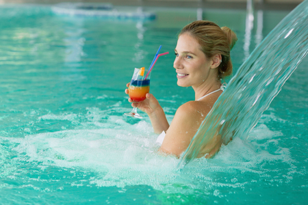 Beautiful attractive woman enjoying time in pool Banco de Imagens