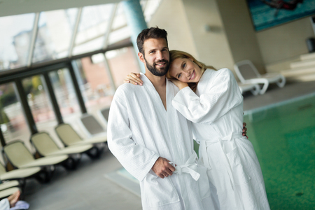 Beautiful cheerful couple relaxing in spa center together
