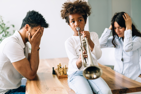 Picture of child making noise by playing trumpet in front of parents Foto de archivo