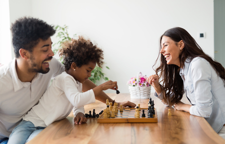 Happy family playing chess together at home Banco de Imagens - 82268013