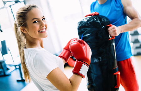 Picture of woman wearing boxing gloves in gym