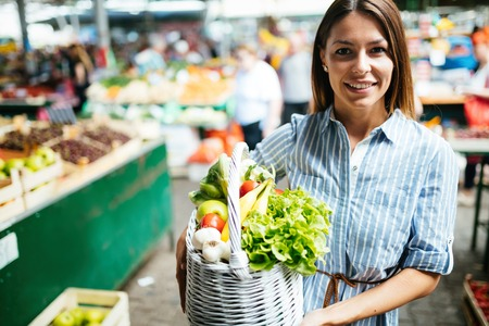Portrait of beautiful woman holding shopping basket Imagens