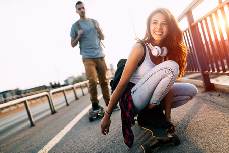 Young attractive couple riding skateboards and having fun 版權商用圖片
