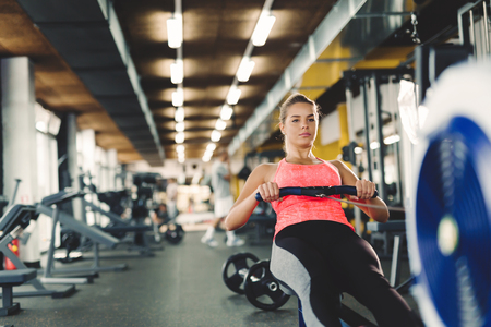 Young cute woman doing exercises with rowing machine