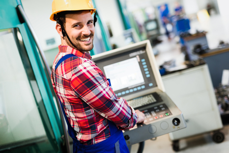 Industry Worker entering data in CNC machine at factory Stock Photo