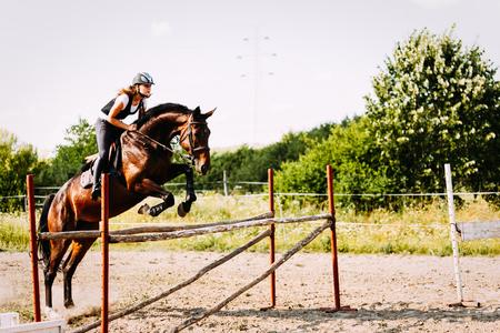 若い女性は、ハードルを飛び越えています馬を騎手します。 写真素材
