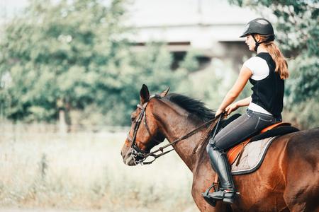 Beeld van jong meisje dat haar paard berijdt