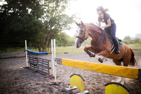 Jeune femme jockey sur le cheval sautant par-dessus obstacle Banque d'images - 84440745