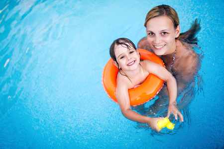 Beautiful woman with her daughter in swimming pool