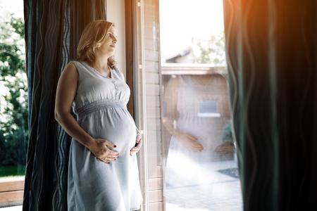 임신 한 여자는 그녀의 배꼽을 잡고