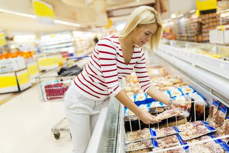 Piękna kobieta kupuje jedzenie w supermarkecie