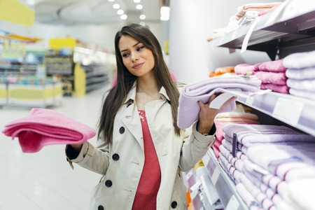 Beautiful woman inspecting and buying towels