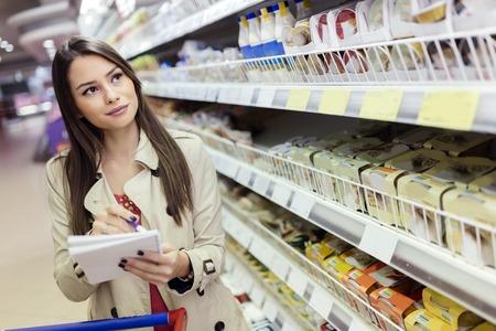 Mooie vrouw die in supermarkt winkelt