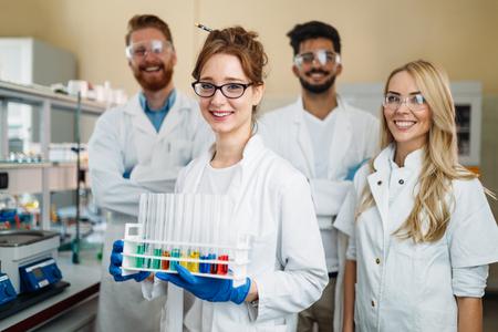 Groep jonge succesvolle wetenschappers die voor camera stellen