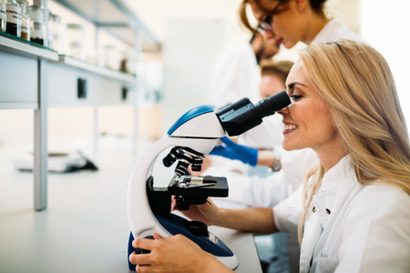 Young scientist looking through microscope in laboratory Stok Fotoğraf