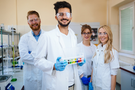 Group of young successful scientists posing for camera Stock Photo