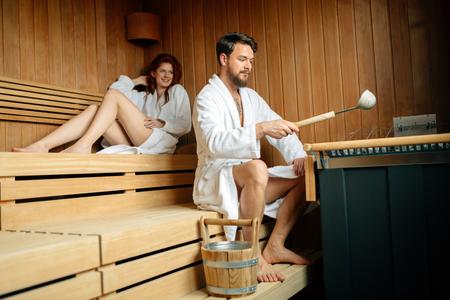 Beautiful couple relaxing in sauna