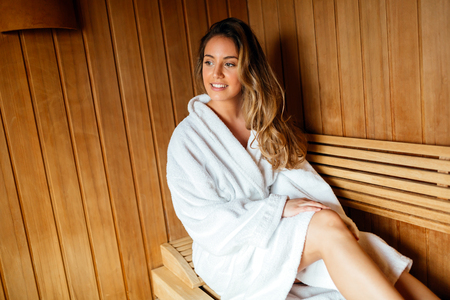 Beautiful woman relaxing in finnish sauna Imagens