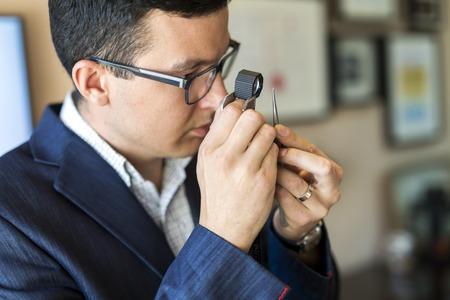 Jeweler looking at diamond through loupe Banco de Imagens