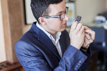 Jeweler looking at diamond through loupe Stock fotó
