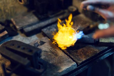 Jeweler melting gold Фото со стока