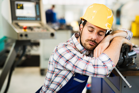 Tired worker fall asleep during working hours in factory