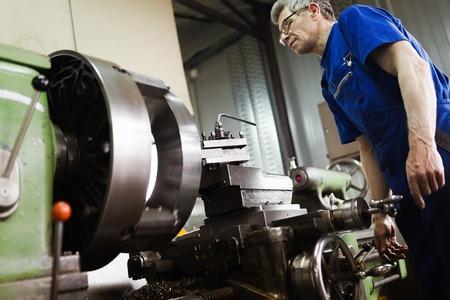 Werknemer in uniform werkt in handmatige draaibank in metaalindustrie fabriek Stockfoto