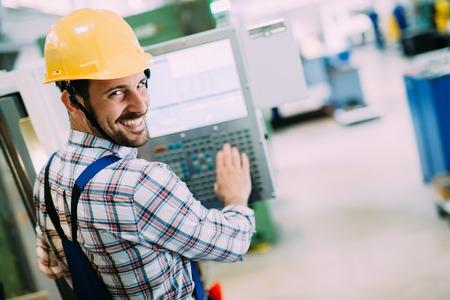 Industriearbeider die gegevens in CNC machine bij fabriek ingaat Stockfoto
