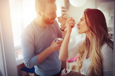 Couple having fun and laughing at home while eating ice cream