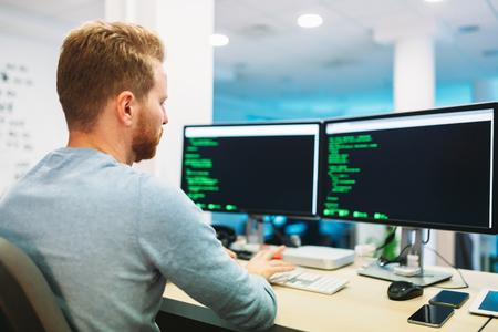 Portrait of young programmer working in office Banco de Imagens