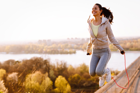 활성 여자가 건너 뛰는 밧줄을 야외에서 점프 스톡 콘텐츠