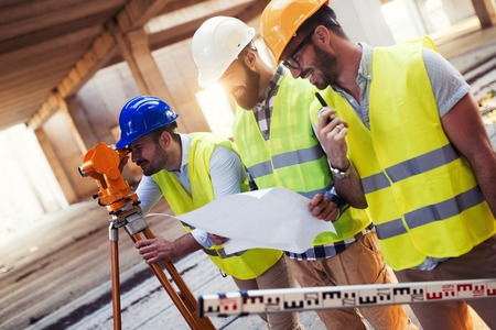 Portret van bouwingenieurs die aan bouwterrein werken