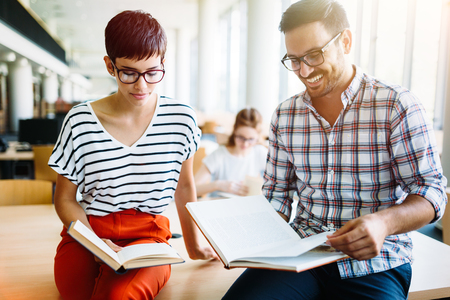 Young attractive students spending time in library Stock Photo