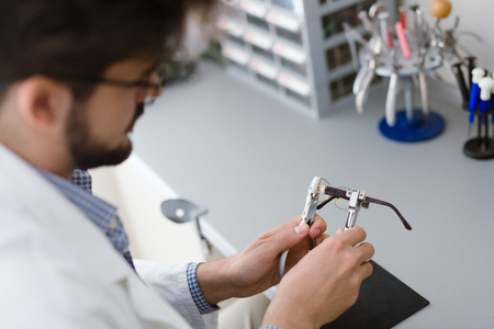 Optician repairing and fixing eye glasses