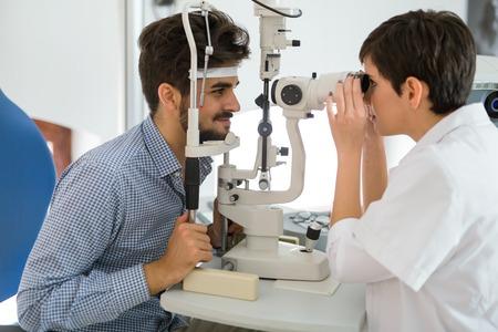 Paciente o cliente en lámpara de queroseno en optometrista o óptico Foto de archivo - 86634777