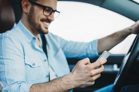 Hombre que usa el teléfono mientras conduce el coche Foto de archivo - 87017519