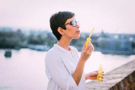 Beautiful dreamy woman blowing soap bubbles outdoor