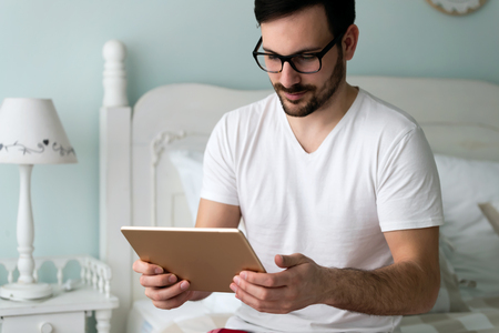 Young handsome man using digital tablet on bed