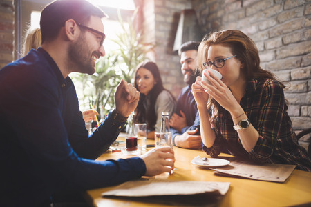 african business: Colleagues from work socializing in restaurant and eating togeth