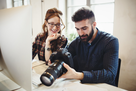 Company photo editor and photographer working together Stock Photo